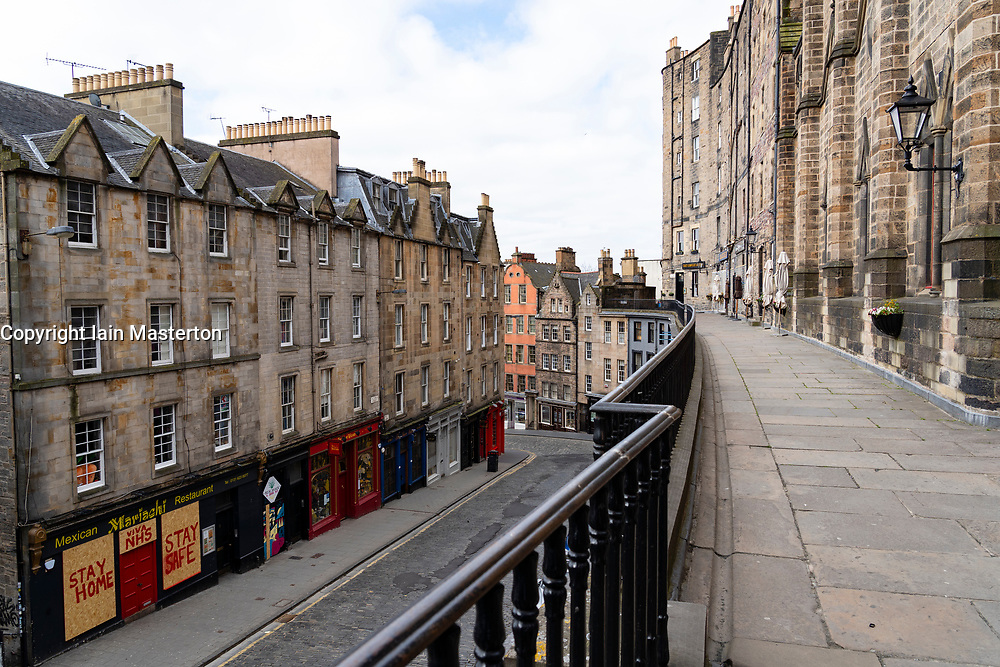 Edinburgh, Scotland, UK. 18 April 2020. Views of empty streets and members of the public outside on another Saturday during the coronavirus lockdown in Edinburgh. Shops and restaurants on Victoria Street are closed and street deserted. Iain Masterton/Alamy Live News