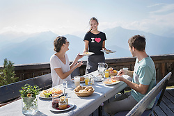 Young woman serving breakfast to couple on terrace, Zillertal, Tyrol, Austria