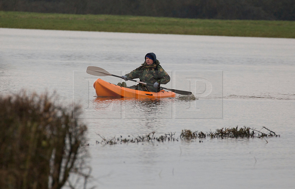 © London News Pictures. 31/01/2014. Muchelney, UK. A man using a canoe to travel over flood water in Muchelney on Somerset Levels, where flood water has cut off parts of the community. Further wet weather at the weekend is due. Photo credit: Ed Stone/LNP
