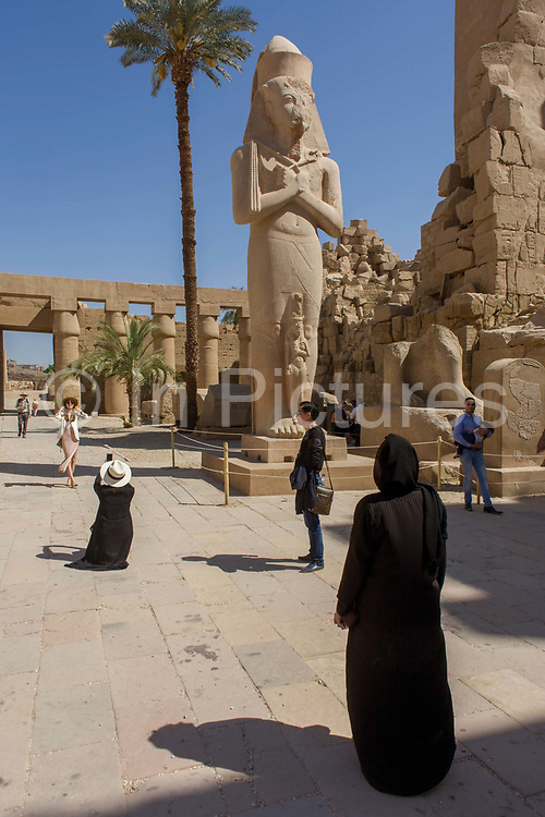 Tourists and the giant colossus of Pharaoh Ramesses ll and his daughter Bintanath at the ancient Egyptian Temple of Karnak, Luxor, Nile Valley, Egypt. Bintanath (or Bentanath) was the firstborn daughter and later Great Royal Wife of the Egyptian Pharaoh Ramesses II and is depicted on statues of her father at least three times in Karnak and Luxor though most famously here. According to the country's Ministry of Tourism, European visitors to Egypt is down by up to 80% in 2016 from the suspension of flights after the downing of the Russian airliner in Oct 2015. Euro-tourism accounts for 27% of the total flow and in total, tourism accounts for 11.3% of Egypt's GDP.