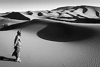 A Merzouga camel man looks across the vast expanse of the Sahara, just after sunrise