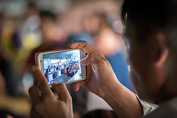 14 September 2018, Damak, Nepal:  Supported by the Lutheran World Federation, the Beldangi refugee camp in the Jhapa district of Nepal hosts more than 5,000 Bhutanese refugees. Here, a man takes a photo as LWF general secretary Rev. Dr Martin Junge visits the camp.