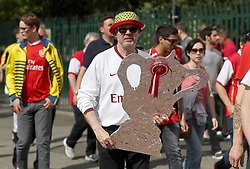 A Arsenal fan holds a foil FA Cup Trophy whilst making his way to the stadium before the Emirates FA Cup Final at Wembley Stadium, London.