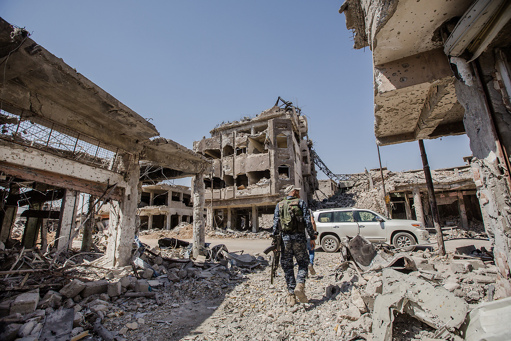 An Iraq federal Police officer walks through the rubble in the old city of Mosul.