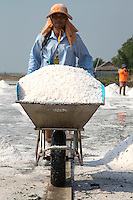 Porter at Samut Sakhon Salt Fields. In Thailand most  salt used comes from brine salt farms, and the largest number of these salt farms are in  the village of Samut Sakhorn near Bangkok. These fields may resemble rice paddis - except for the important absence of rice.  To make salt the fields are flooded with sea water pumped in from the Gulf of Thailand, and left to dry naturally in the sun. It takes about one month for the water to evaporate and create salt.  When the water has evaporated, the salt is piled into mounds and cleaned and bagged for sale.  Along Highway 35 there are vendors along the roadside selling huge bags of salt.