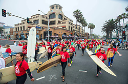 June 20, 2017 - Huntington Beach, California, USA - Some of the nearly 600 surfers cross Pacific Coast Highway at Main Street in downtown Huntington Beach Tuesday morning as they head for the ocean to create the world's largest paddle out ''Circle of Honor'' in Huntington Beach Tuesday morning, June  20, 2017. (Photo by Mark Rightmire, Orange County Register/SCNG) (Credit Image: © Mark Rightmire, Mark Rightmire/The Orange County Register via ZUMA Wire)