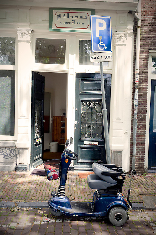 Een scootmobiel staat op de invalidenparkeerplaats voor de El Fath moskee in het centrum van Utrecht.<br /> <br /> A scooter is parked on a disabled parking in front of the El Fath mosque in Utrecht.
