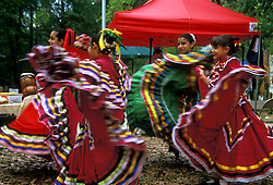 Stock photo of a group of young girls in traditional dresses dancing at a Cinco De Mayo Celebration