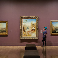London, UK - 8 September 2014: a gallery assistant looks up at 'The Death of Actaeon, with a Distant View of Montjovet, Val D'Aosta, c 1837' by J.M.W. Turner, during the press preview of The EY Exhibition: Late Turner – Painting Set Free exhibition at Tate Britain