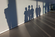 The silhouettes of airport passengers against a wall in the terminal as they have disembarked from their flight, on 10th July 2016, at Lisbon, Portugal. Several people are in a line next to each other, their outlines defined and their shadows stretching across the terminal floor.