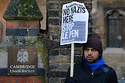 © Licensed to London News Pictures. 19/02/2013. Cambridge, UK A man holds a banner at the entrance. Unite Against Fascism holds a demonstration and Rally today,19th February, outside the Cambridge Union debating society, against Marine Le Pen who has been invited to address the Union. Marine Le Pen is the President of the Front National, the third largest political party in France.  As a long-standing MEP, she has become a highly influential figure on the European right . Photo credit : Stephen Simpson/LNP