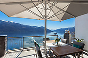 Terrace of house with dining table and lake view