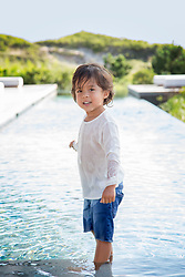 little boy standing in a swimming pool