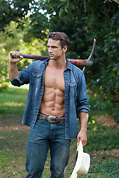 handsome man with a pick axe and a cowboy hat outdoors