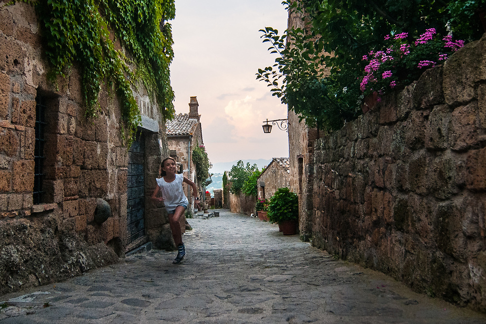 """A girl runs towards the streets of the village of Civita di Bagnoregio.<br /> Civita di Bagnoregio is a town in the Province of Viterbo in central Italy, a suburb of the comune of Bagnoregio, 1 kilometre (0.6 mi) east from it. It is about 120 kilometres (75 mi) north of Rome. Civita was founded by Etruscans more than 2,500 years ago. Bagnoregio continues as a small but prosperous town, while Civita became known in Italian as La città che muore (""""The Dying Town""""). Civita has only recently been experiencing a tourist revival. The population today varies from about 7 people in winter to more than 100 in summer.The town was placed on the World Monuments Fund's 2006 Watch List of the 100 Most Endangered Sites, because of threats it faces from erosion and unregulated tourism."""