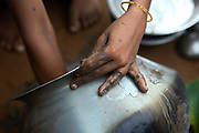 Tabasum Khatun, 14, is washing a metal pot in the courtyard of her home in Algunda village, pop. 1000, Giridih District, rural Jharkhand, India.