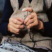 Maria Streulea, a Romanian peasant farmer, crochets the edge to a handwoven bag, the design typical to the Saxon Transylvania region, Saliste, Romania