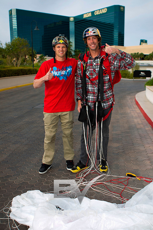 From left Erik Roner of Nitro Circus assists Travis Pastrana as he gathers his parachute after base jumping off The Signature at the MGM Grand Hotel & Casino on Wednesday June 1, 2011 in Las Vegas to promote the North American debut of Nitro Circus Live at the MGM Grand Garden Arena on Saturday June 4, 2011. (Jeff Bottari/AP Images for Nitro Circus Live)