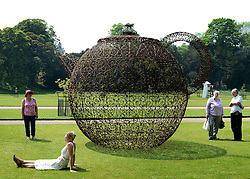 © Licensed to London News Pictures. 24/05/2012. Waddesdon, UK. People relax around Joana Vasconcelos' sculpture of a teapot. People enjoy the warm weather amongst an exhibition of contemporary sculpture at Waddesdon Manor, Buckinghamshire, today 24th May 2012. The exhibition is being held by Christie's as part of a private sale. Photo credit : Stephen Simpson/LNP