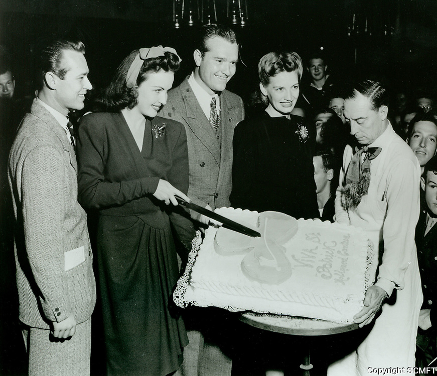 1943 (L to R) Jess Barker, Genny Simms, Red Skelton, Edna Skelton, and Buster Keaton during the cake cutting ceremony on St. Patrick 's Day at the Hollywood Canteen