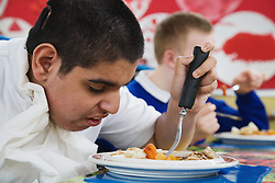 Boy with physical and learning difficulties eating his school dinner,