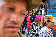 16 JUNE 2014 - POIPET, CAMBODIA:  Cambodian migrants get off a bus in Poipet, Cambodia. More than 150,000 Cambodian migrant workers and their families have left Thailand since June 12. The exodus started when rumors circulated in the Cambodian migrant community that the Thai junta was going to crack down on undocumented workers. About 40,000 Cambodians were expected to return to Cambodia today. The mass exodus has stressed resources on both sides of the Thai/Cambodian border. The Cambodian town of Poipet has been over run with returning migrants. On the Thai side, in Aranyaprathet, the bus and train station has been flooded with Cambodians taking all of their possessions back to Cambodia.   PHOTO BY JACK KURTZ