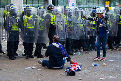 Glasgow, Scotland, UK. 15 May 202. Rangers football supporters  celebrating 55th league victory are cleared from George Square by police in riot gear on Saturday evening. In very violent scenes police were pelted with bottles and items from a nearby construction site as police pushed the supporters into the south west corner of the square. Pic; Man falls to ground in front of police line. Iain Masterton/Alamy Live News.