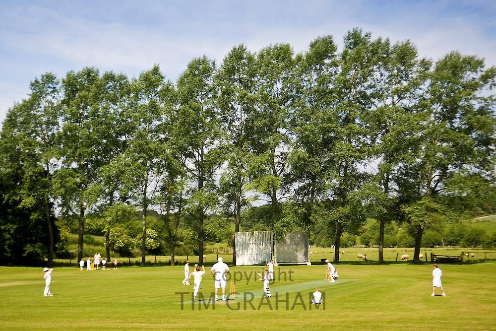Children play cricket on village pitch, Swinbrook, The Cotswolds, England, United Kingdom