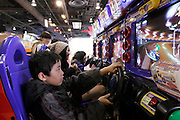 Young friends playing in a video game arcade Japan