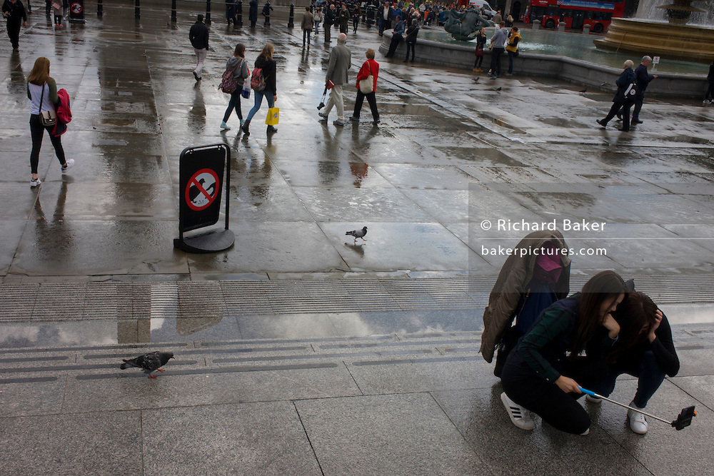 Tourists take selfies on the ground while pigeons stalk the pavements in London's Trafalgar Square.
