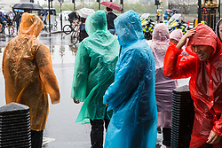 London, UK. 19 July, 2019. Tourists in rain ponchos brave heavy rain close to the Houses of Parliament in Westminster.