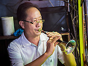 "14 MAY 2015 - BANGKOK, THAILAND: A musician plays the suona, also called a laba, during a Chinese opera in the Pek Leng Keng Mangkorn Khiew Shrine in the Khlong Toey slum in Bangkok.  Chinese opera was once very popular in Thailand, where it is called ""Ngiew."" It is usually performed in the Teochew language. Millions of Chinese emigrated to Thailand (then Siam) in the 18th and 19th centuries and brought their culture with them. Recently the popularity of ngiew has faded as people turn to performances of opera on DVD or movies. There are still as many 30 Chinese opera troupes left in Bangkok and its environs. They are especially busy during Chinese New Year and Chinese holiday when they travel from Chinese temple to Chinese temple performing on stages they put up in streets near the temple, sometimes sleeping on hammocks they sling under their stage. Most of the Chinese operas from Bangkok travel to Malaysia for Ghost Month, leaving just a few to perform in Bangkok.       PHOTO BY JACK KURTZ"