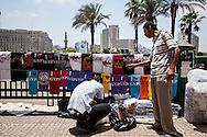 A vendor in Cairo's Tahrir square sells T-shirts to demonstrators against the country's president Mohammed Morsi, one year after he was elected. Cairo, Egypt.
