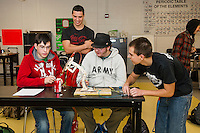 """Trevor Blake, Brian Engelsen, Andrew West and Michael Hodge use pin point precision to maneuver their """"Robot Arm"""" during Joanne Gilbert's CCR Applied Physics class at Laconia High School Monday morning.  (Karen Bobotas/for the Laconia Daily Sun)"""