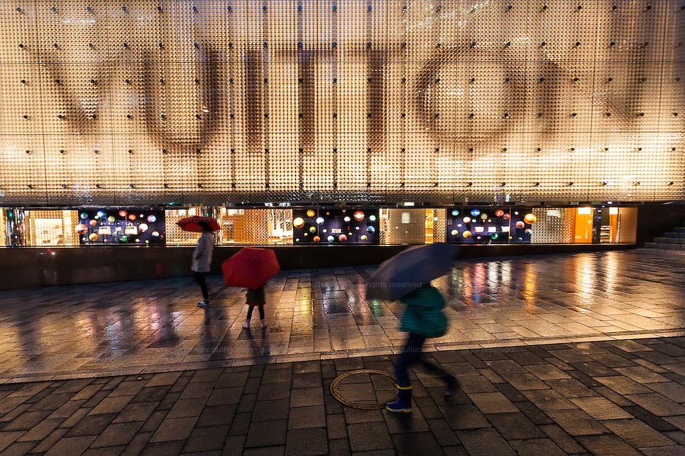 A daily with umbrellas walk in the rain in front of a Louis Vuitton store in Roppongi,  Tokyo, Japan. Friday October 28th 2016