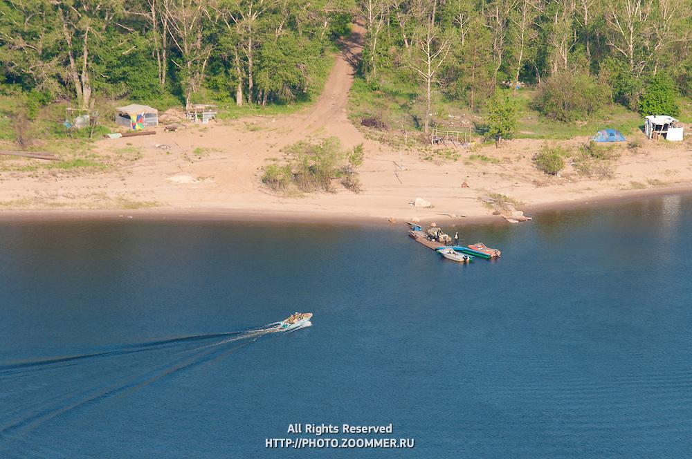 Quay with motor boats and a camp on island in Volga near Samara city