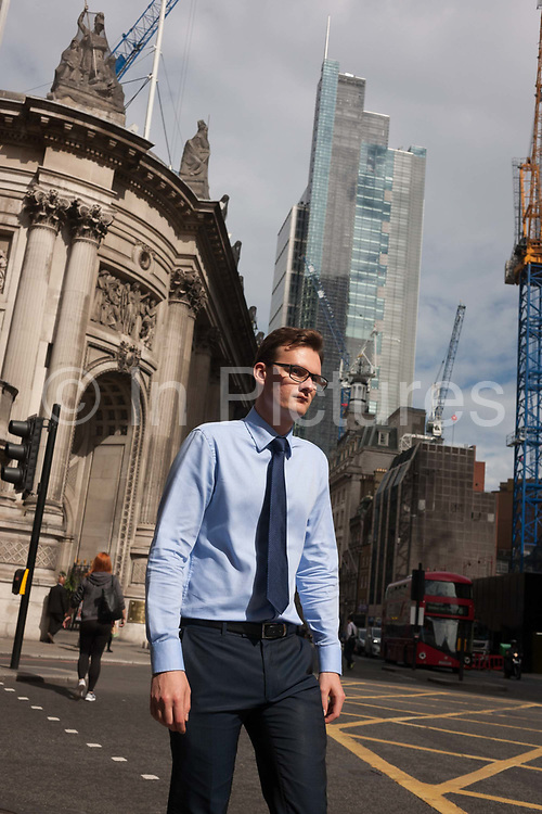 A young businessman in glasses and matching blue menswear, a style much-copied in 2016, walks along Bishopsgate on 12th September, in the City of London, UK.