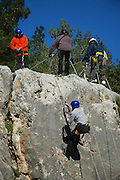 Israel, Carmel Mountain, a group of mountaineers rappelling down a cliff