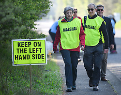 © Licensed to London News Pictures. 19/04/2019. Maidenhead, UK. Prime Minister THERESA MAY  helps out as a marshal with her husband PHILIP MAY, at the Maidenhead Easter 10 run in her constituency of Maidenhead in Berkshire. Parliament currently on Easter recess after an extension to Article 50 was granted by the EU. Photo credit: Ben Cawthra/LNP