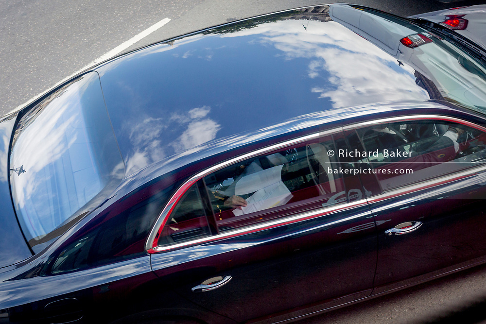 An aerial view of a VIP's car and the paperwork being read through by its passenger while being under police escort around Trafalgar Square on 5th June 2019, in London, England.