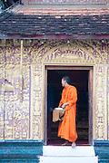 Wat Xiengthong, Luang Prabang, Laos. Monk leaving offering.