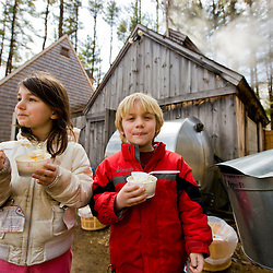 A brother and sister sample ice cream and fresh maple syrup at a sugar house in New Hampshire.