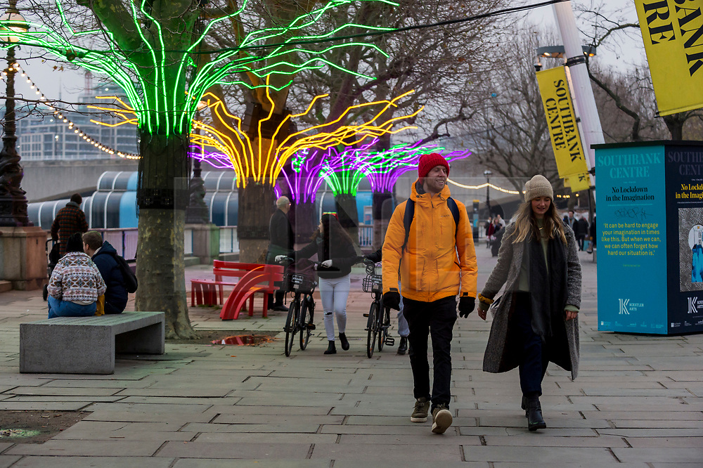 """© Licensed to London News Pictures. 07/12/2020. LONDON, UK. Members of the public walk by """"Lumen"""" by David Ogle, trees illuminated with glowing neon flex. Preview of """"Winter Light"""" presented by Southbank Centre.  Over 15 artworks and new illuminated commissions by a range of leading international artists are on display around the site's buildings and the Riverside Walk until the end of February 2021.  Photo credit: Stephen Chung/LNP"""