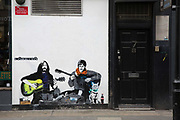 Soho Beatles street art featuring John Lennon and Paul McCartney busking with coloured guitars and a cat on the 23rd March 2018 in Central London, United Kingdom.