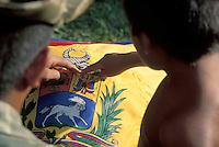 Soldado militar enseñando a niño Yanomami el escudo de la bandera venezolana, Parima, Amazonas, Venezuela.