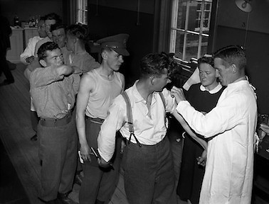 Pte. K O'Sullivan and men from the 6th Battalion line up to be vaccinated against yellow fever by Comdt Laurence O'Toole, Army Medical Corps. The troops were on their way to the Congo. .22.07.1960<br /> We have been advised by Conan Kennedy that this is Tony Cahill, widely known in military circles at the time as 'Doc'. Thanks Conan we always welcome better information to improve our records