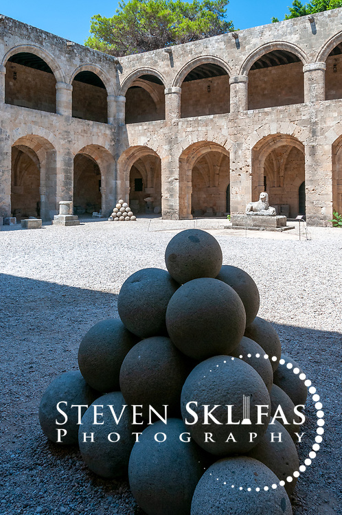 Rhodes. Greece. Stacked stone mortar balls in the stunning internal courtyard of the gothic Knights hospital in the Old Town. Completed in 1484, the hospital was used in times of war to nurse the sick and injured from all over Christian Europe. T