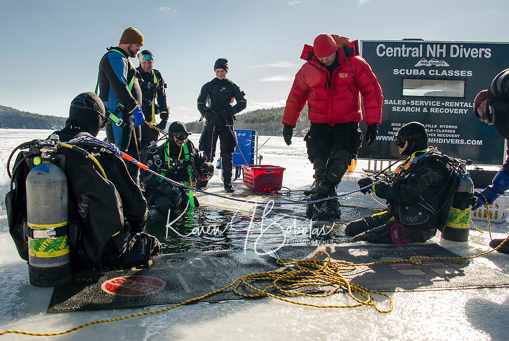 PJ Concannon and Jane Sellers prepare to submerge for a 35' ice dive with the East Coast and Central NH Divers during their demo and training Saturday afternoon on Meredith Bay.  (Karen Bobotas/for the Laconia Daily Sun)