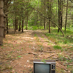 A discarded television on a trail in the forest near Marquoit Bay in Brunswick, Maine.