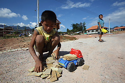 Children playing with a toy construction truck on a new road in the relocation village of Ban Tasala, Bolikhamsay Province, Lao PDR